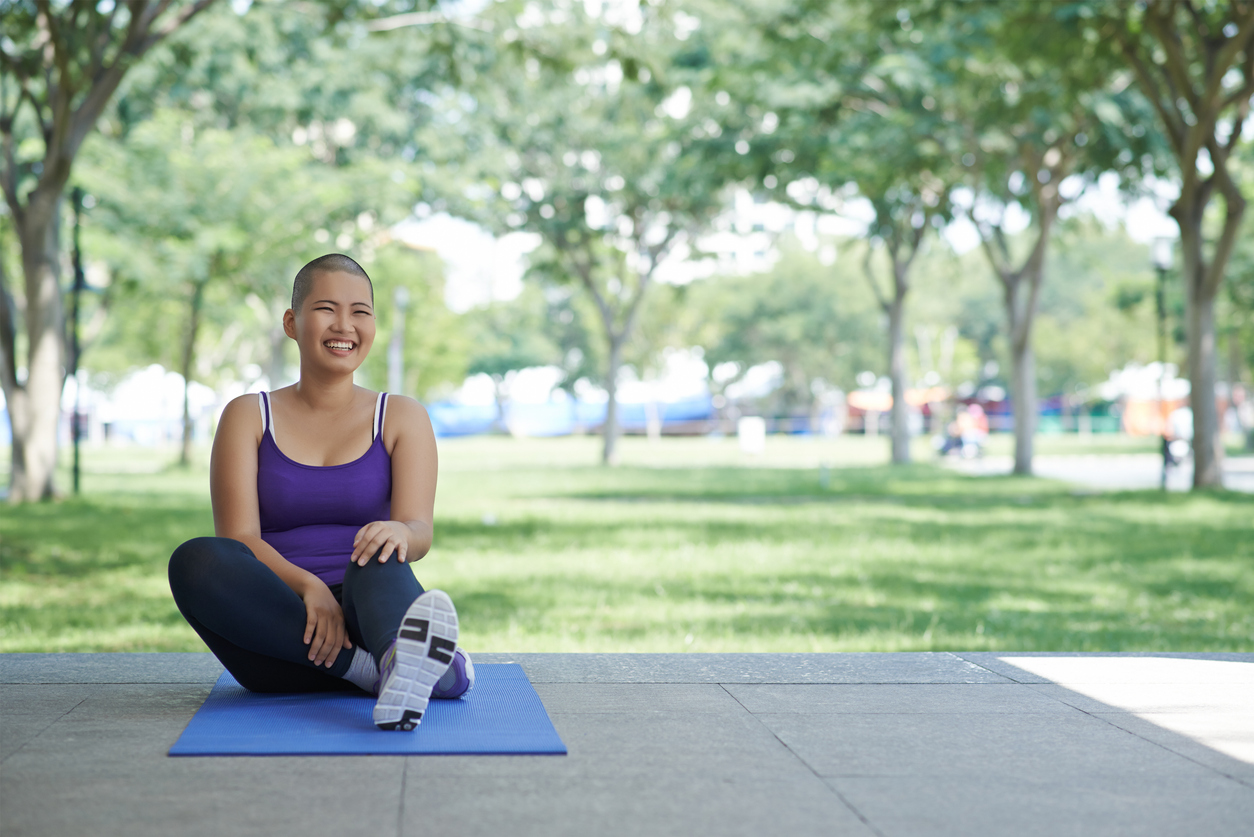 Bald woman sitting on yoga mat happy