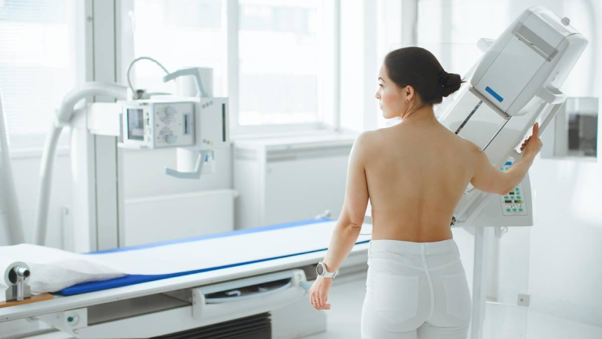 Woman standing waiting for a mammogram.